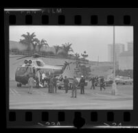 President Johnson and Lynda Bird exit helicopter in parking lot at Century Plaza. A. 1967.