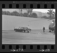 Presidential limousine awaits Lyndon Johnson and Lady Bird, who have exited a helicopter, out of frame to the right, 1967.