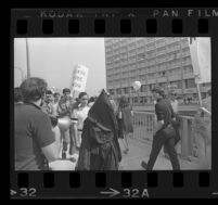 Protester wearing a black hood and robe outside of Century Plaza Hotel, where President Johnson is scheduled to arrive, 1967.