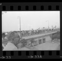 Onlookers and protesters await President Johnson's motorcade on Avenue of the Stars in Century City, 1967.