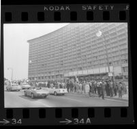 Crowd (including protesters) gathers outside of Century Plaza Hotel in anticipation of President Johnson's arrival, 1967.