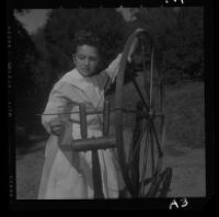 Carla Mitchell, a student at University Elementary School, spins yarn on spinning wheel of Pilgrim era, 1958.