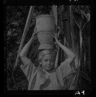 Kristen Commons, University Elementary School pupil, carries mortar on her head, 1958.