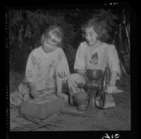Betsy Brown, right, grinds maize while Susan Wright prepares it for cooking, 1958.