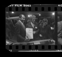 Tom Bradley holds sign for Freedom of Press exhibit while at reception for the event with Otis Chandler and Hugh Hefner. A. 1980.