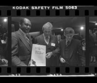 Tom Bradley holds sign for Freedom of Press exhibit while at reception for the event with Otis Chandler and Hugh Hefner. B. 1980.