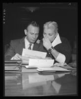 Barbara Payton holds her nose as she inspects summons with attorney Milton Golden, Los Angeles, 1955