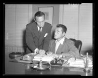 Tom Neal (right) and Attorney Milton golden discuss fight between the former and Franchot Tone, which left the latter hospitalized, 1951.
