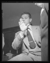 Tom Neal, being questioned in th eoffice of District Attorney S. Ernest Roll, waves hand to deny initiating the fight that landed Franchot Tone in the hospital, 1951.