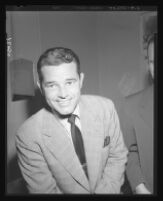 Tom Neal smiles to the camera in District Attorney S. Ernest Roll's office during questioning regarding his fight with Franchot Tone, 1951.