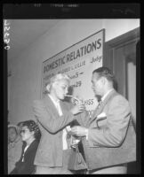Barbara Payton has cigarette lit by Attorney Milton Golden at Courthouse during proceedings for her divorce from Franchot Tone, 1952.