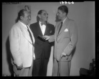 Ronald Reagan presents Attorney Laurence W. Beilenson with an honorary gold membership to the Screen Actors Guild as Edward Arnold watches, 1949.