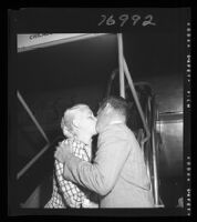 Tom Neal and Barbara Payton kiss at the airport before Payton's trip to London, 1952.