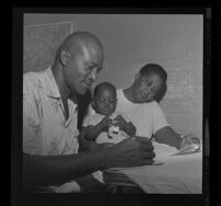 Peola Denham works on family budget with wife, Fannie, and son, Charles, 1962.