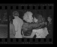 Dorothy Buffum Chandler (left), grandmother of Harry Brant Chandler, embraces Denise Hardré during the wedding of Hardré and Chandler, 1979.