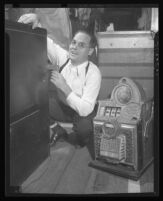 Rev. Wesley Anderson poses in front of a safe and next to a slot machine, 1945.