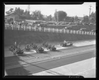 Motorcycles on Arroyo Seco Parkway as military trucks exit at dedication of the highway, Los Angeles, 1940