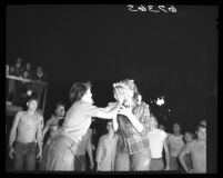 Carol Cregar, UCLA freshman vice-president, heaves pie in face of sophomore Gwin Allenberg, 1950.