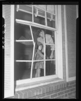 Mrs. William Gude and daughter Wendy look through shattered window, Brentwood (Los Angeles), 1950