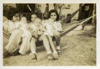 Three little girls holding babies