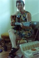 Amy Denio with acoustic guitar and accordion [descriptive].