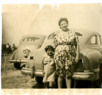 Woman with girl in front of car