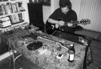 Jeff Gburek seated, playing guitar, 2004 [descriptive]