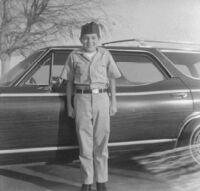 Boy in uniform by car