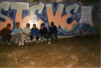 Guys posing by graffiti mural