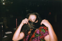 Woman covering her face at bar