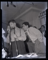 William Elconin, of CIO electrical workers union and Jeff Kibre on stage during aircraft workers' rally, 1941.