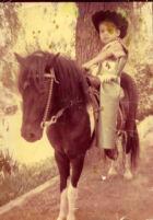 Boy dressed as cowboy on horse