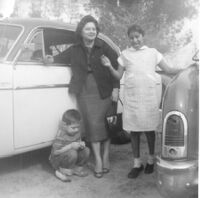 Woman standing with children between two cars
