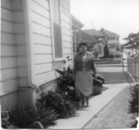 Woman standing next to house