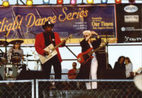 Bo Diddley and an unidentified guitarist and drummer performing at the Santa Monica Pier Twilight Dance Series, July 9, 1998 [descriptive]