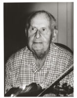 Stéphane Grappelli holding a violin, Los Angeles, August 1995 [descriptive]