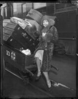 Clara Bow, with Santa Fe Railway pushcart full of luggage.