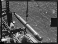 Torpedo suspended above the ocean by a cable next to a ship or dock