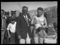 """Fastest Man Alive"" and 100-meter gold medalist Charlie Paddock stands with A.A.U. chief Robert Weaver and revelers, 1920s."