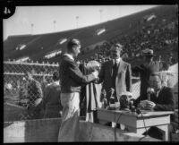 E. Manchester Boddy awards football trophy to Oliver Anderson at the Coliseum, Los Angeles, 1930s