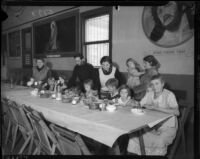 Group of women and children displaced by flood; eating at table in Salvation Army center in Venice, Calif., 1934