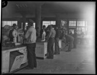 Unidentified men weigh goods at a cooperative, Los Angeles, 1930s