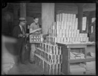 Two unidentified men move canned goods, Los Angeles, 1930s