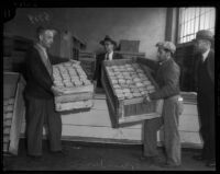 Unidentified men move goods in wooden crates, Los Angeles, 1930s