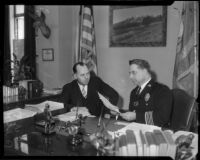 Chief of the L.A.P.D. James E. Davis speaks with Capt. William F. Hynes in his office, circa 1934.