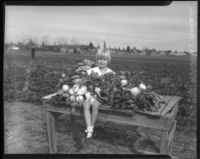 Young girl sits amongst the harvest from a community garden, circa February 1934.
