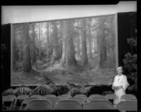 Martella Lane, painter, poses with painting of California Redwoods, [1925?]