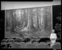 Martella Lane poses with painting of California Redwoods
