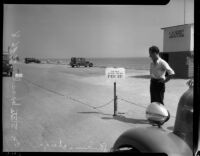 Unidentified man stands next to parking charge sign at state beach, Los Angeles, 1930s