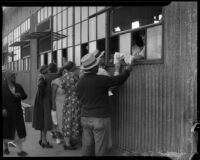 Unidentified men and women receive sacks of flour at a county food exchange program, Los Angeles, 1930s